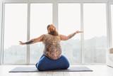 Calm fat man meditating near window