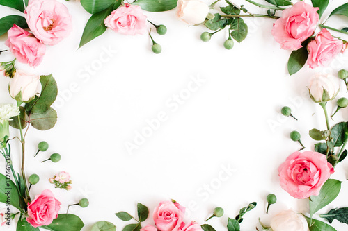 Round frame made of pink and beige roses, green leaves, branches on white background. Flat lay, top view. Valentine's background