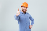 Cheerful bearded man in helmet standing and showing thumbs up