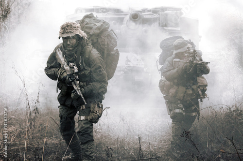 Jagdkommando soldiers Austrian special forces and tank moving on terrain in the fog