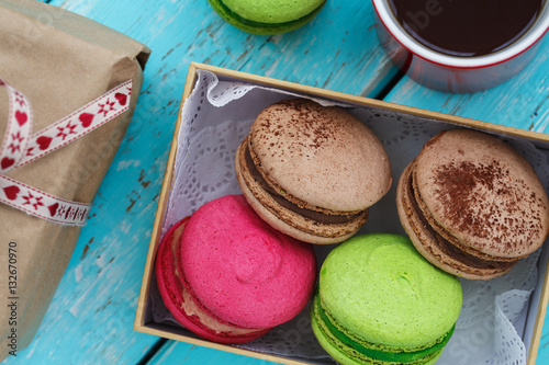 Póster Macaroon cakes in a box and mug of tea with gift, top view
