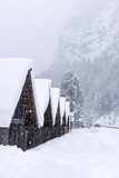 Wooden Mountain Houses in Winter Forest While Snowing. Winter Idyll.