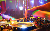 Fototapety Close up of dj playing party music on modern cd usb player in disco club - Nightlife and entertainment concept - Defocused background with shallow depth of field and focus on buttons near mixing hand