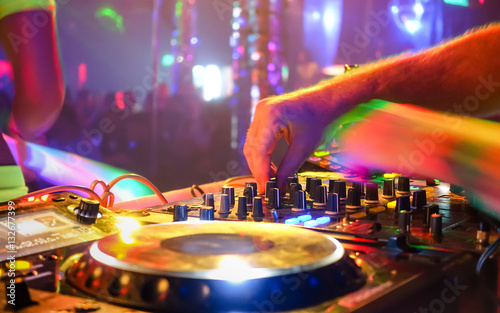 Foto Murales Close up of dj playing party music on modern cd usb player in disco club - Nightlife and entertainment concept - Defocused background with shallow depth of field and focus on buttons near mixing hand