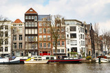 Traditional old buildings, canal and boat in Amsterdam, the Netherlands