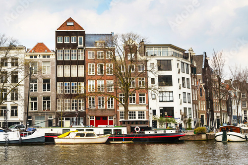 Traditional old buildings, canal and boat in Amsterdam, the Netherlands Poster