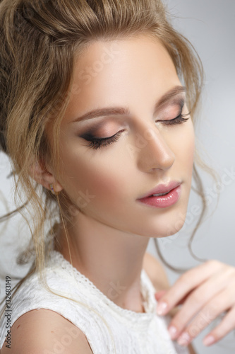 Pretty bride with a gentle make-up isolated on a gray background. © ksi