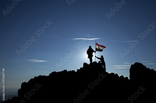 Poster Two soldiers raise the Syrian flag on top of the mountain