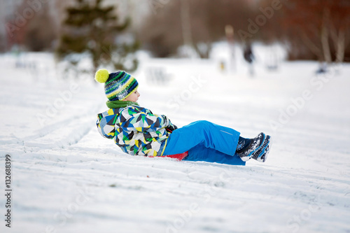 Fotografiet Cute child, boy, sliding with bob in the snow, wintertime