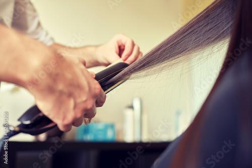 Poster stylist with iron straightening hair at salon