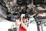 Automechaniker repariert defektes Fahrzeug auf der Hebebühne in einer Werkstatt  - 132691588