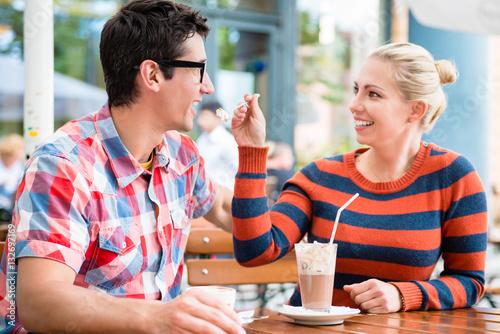 Poster Paar, Frau und Mann, trinkt Kaffee in einem Straßencafe in Berlin