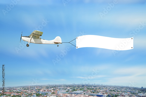 Poster Antique Airplane with advertise board fly on Cityscape bird eye