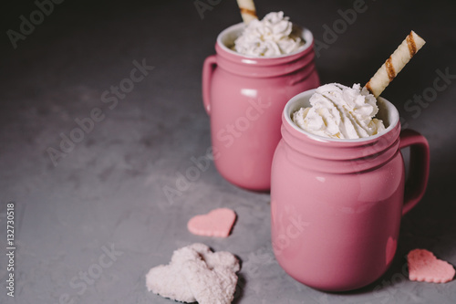 Two pink mugs with hot chocolate and cream on a gray concrete background. Drinks for a loving couple. The concept of Valentine's Day.