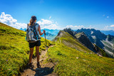 Hiker in boots and backpack holds walking stick - 132732771