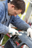 Man worker repairing bumper car with putty and spatula tool