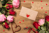 Roses, message card  and red ribbon on wooden background. Valentines day background