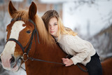 Young rider girl with long hair lying on horse neck. Friendship background