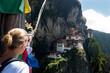 Постер, плакат: Bhutan Taktshang monastery Tigers Nest temple blonde woman looking the landmark on a mountain with prayer flags