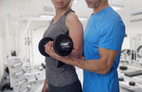 Personal trainer helping woman working with dumbbells at gym