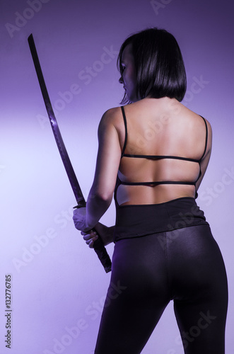 Poster Sexy girl , back view holding samurai sword, purple background