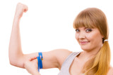 Fit girl with measure tape measuring her biceps