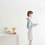 キッチンで食器を運ぶ女性