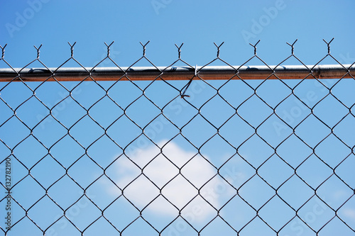 Poster iron chainlink fence against sky