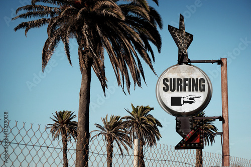 Poster aged and worn vintage photo of surfing sign with palm trees