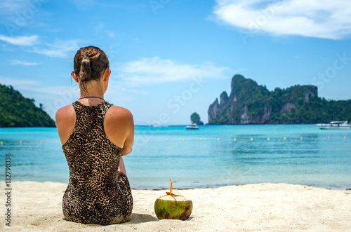 Poster Rear view of a girl sitting on the white sand with coconut cocktail in fabulous bay of Phi Phi island, Thailand