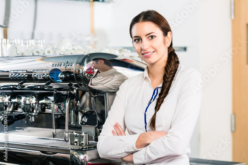 Poster Portrait of young waitress smiling near the coffee machine