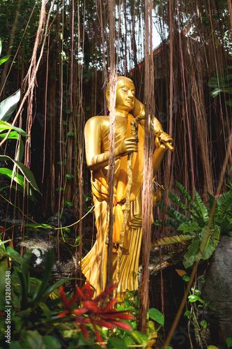 Plagát Golden sculpture in bushes