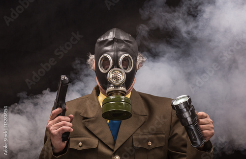 Poster Portrait of a soldier in a gas mask with a gun on a black background isolated