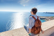 Young woman traveler sitting overlooking the sea. Travel to Gree