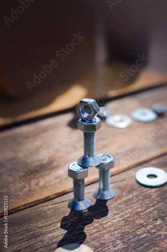 Poster A figure of one small robot assembled from several bolts and nuts standing in a vertical position on a table made of planks
