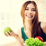 Smiling woman with plate of fruits, indoors