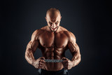 Portrait of aggressive bodybuilder trying to tear the metal chain. Isolated