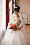 Wedding bride posing near window after wedding preparation. Wedding portrait of beautiful bride