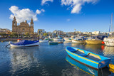 Msida, Malta - Traditional blue painted maltese fishing boat with Msida Parish Church at background on a blue sky summer day
