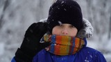boy standing outside in snowy weather and waves at the camera.