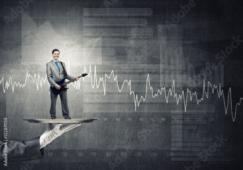 Poster Businessman on metal tray playing electric guitar against graphs background