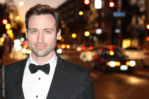 Sexy man in tuxedo and bow tie posing in the city streets at night