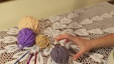 A young girl unravels a ball of yarn for knitting.