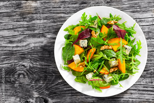 persimmon salad with lettuce leaves, blue cheese and walnuts