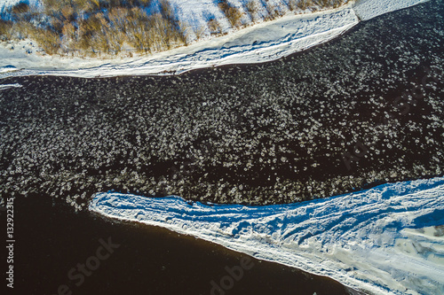 Plakát Winter river with ice floes, drone aerial image