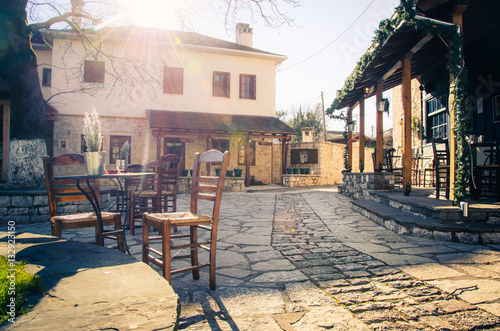Small traditional paved square with cafe and authentic narrow streets in Nissaki, Ioannina, Greece