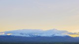 Timelapse shot of cloudscape rolling over mountains. Idyllic view of landscape against sky. Scenic view of mountain range during sunset. 4K resolution.