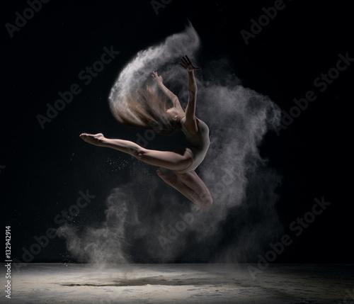 Tuinposter Gymnastiek Girl in body jumps in dust cloud black background