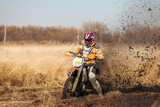 Enduro bike rider on a field with dry grass in autumn. The motor