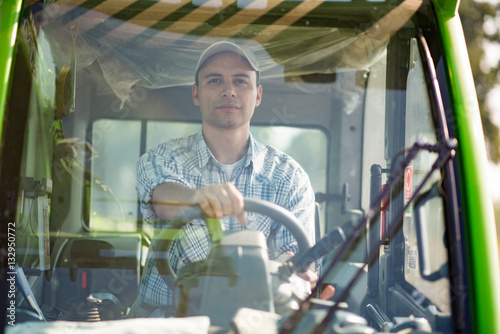 Poster Smiling farmer driving an harvesting machine